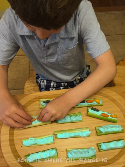 Jackson adds goldfish to celery sticks with colored cream cheese