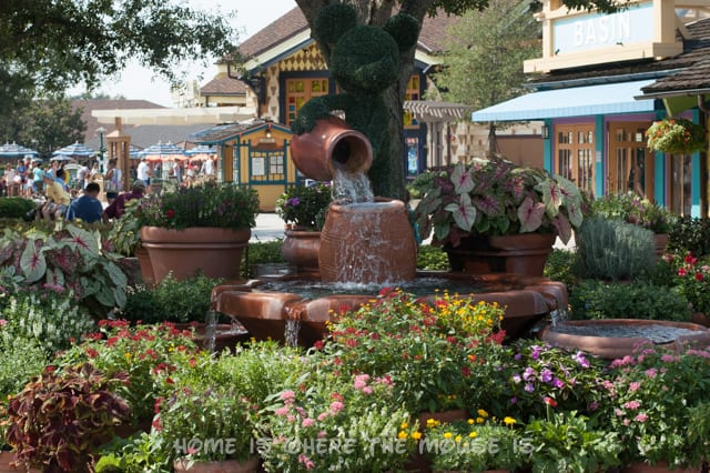 Mickey Mouse topiary is pouring water into flower pots at this Downtown Disney fountain